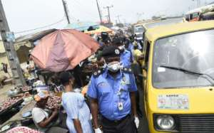 Lagos Police Commissioner Hakeem Odumosu squeezes his way through a market to monitor compliance with measures to curb the spread of coronavirus.  By PIUS UTOMI EKPEI (AFP)
