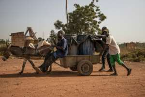 Latrine workers haul away barrels filled with human waste -- Ouagadougou's sewage farms are located far away, which means the contents often get dumped on land on the city's outskirts.  By OLYMPIA DE MAISMONT (AFP)