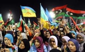 Libyan women wave their new national flag and the flag of the Berber during an Amazigh festival in Tripoli on September 27, 2011