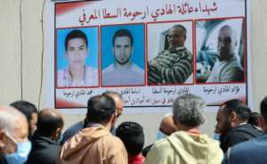 Libyans gather by a wall poster depicting victims from one family during a funeral procession for 12 bodies that were identified from mass graves found in Tarhuna town.  By Mahmud Turkia (AFP)