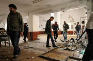 Libyans inspect the interior of a mosque in Benghazi on February 9, 2018, after it was hit by a twin bomb attack