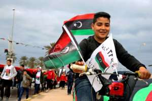 Libyans processed through the capital Tripoli waving the national flag as part of celebrations marking the anniversary of the 2011 NATO-backed uprising that toppled longtime dictator Moamer Kadhafi.  By Mahmud TURKIA (AFP)