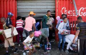 Looters stole items from shops they believed to be foreign-owned during a riot in a Johannesburg suburb.  By GUILLEM SARTORIO (AFP)