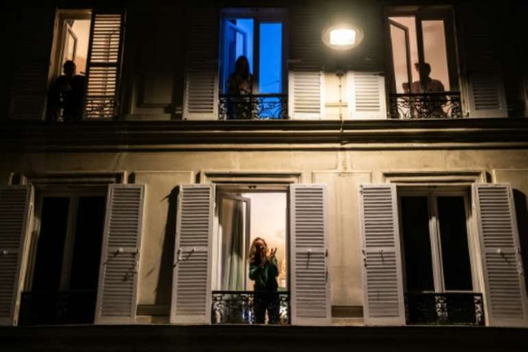 Locked down residents in Paris applaud healthcare employees from their windows. By Martin BUREAU (AFP)