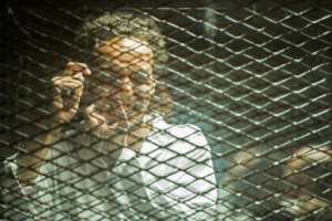 Mahmoud Abu Zeid mimics taking a photograph during his trial at the Cairo Criminal Court on September 8.  By Mohamed el-Shahed (AFP)