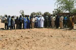Malian President Ibrahim Boubacar Keita, centre, visited the village on Monday, standing at a mass grave. By Handout (MALIAN PRESIDENCY/AFP)