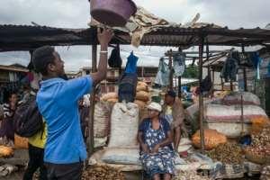 Market trader Nirina Ravololona, seated, says her natural mixes can give the virus a 'good hiding'.  By RIJASOLO (AFP)