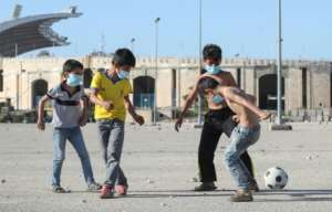 Mask-clad boys play football in the Lebanese capital Beirut.  By - (AFP)