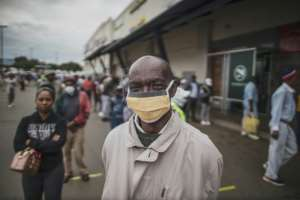 Masked: An elderly man in the Johannesburg suburb of Soweto waits in line at a pay point operated by South Africa's Social Security Agency.  By MARCO LONGARI (AFP)