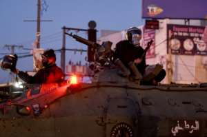 Members of Tunisia's National Guard sit atop an armoured personnel carrier to stop protesters.  By FETHI BELAID (AFP)