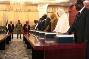Members of the Sudanese cabinet are sworn in in the presence of new Prime Minister Abdalla Hamdok (back-L) and General Abdel Fattah al-Burhan (back-C), the head of Sudan's ruling sovereign council, at the presidential palace in Khartoum.  By Ebrahim HAMID (AFP)