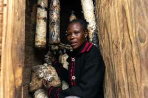 Memory Ruvinga and the mushrooms she grows as an additional source of income -- a scheme introduced by the Danish charity DCA.  By Jekesai NJIKIZANA (AFP)