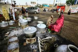 Men and women prepare food for the demonstrators just before the time for breaking the fast during the holy month of Ramadan. By ASHRAF SHAZLY (AFP)