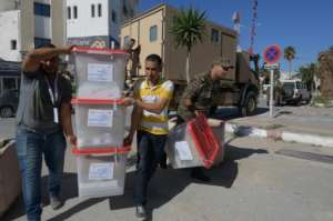 Men from Tunisia's election commission and members of the military deliver blank ballots to a polling station in the capital a day before the presidential runoff.  By FETHI BELAID (AFP)