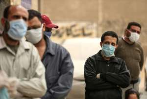 Men wait outside a centre of the non-governmental Egyptian Food Bank to receive cartons with foodstuffs in April.  By Mohamed el-Shahed (AFP/File)