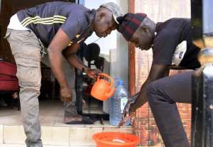 Men wash their hands before entering a restaurant in Dakar.  By Seyllou (AFP)