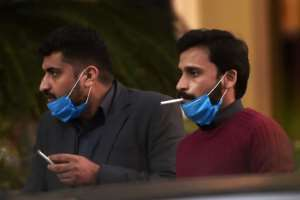 Men wearing masks smoke outside a Pakistan-based Chinese company in Islamabad.  By Aamir QURESHI (AFP)