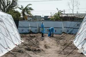 Medical staff disinfect themselves beside treatment tents at Macurungo, where one senior official warned more beds were urgently needed while doctors and nurses said they fear the worst is yet to come. By Yasuyoshi CHIBA (AFP)