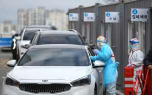 Medical staff take samples from passengers with suspected symptoms of the COVID-19 coronavirus at a drive-through screening clinic of a hospital in Daegu.  By - (YONHAP/AFP)