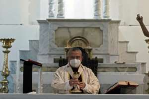 Mexican Archbishop Francisco Moreno Barron wears a face mask as he celebrates Easter Mass at the empty cathedral in Tijuana.  By Guillermo Arias (AFP)
