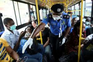 Mind the gap: Lagos Police Commissioner Hakeem Odumosu, pictured in March, as he urges social distancing on a city bus. Public transport, streets and markets are notoriously crowded, making it hard for Lagosians to keep their distance.  By PIUS UTOMI EKPEI (AFP)