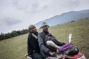 Minembwe's mayor Gadi Muzika, left, rides back to town after the funeral.  By ALEXIS HUGUET (AFP)
