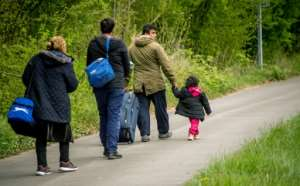 Migrants are seen walking in northern France in 2017, the y ear after the UN says people-smuggling rings earned some $7 billion -- an amount equal to US and EU humanitarian aid that year.  By PHILIPPE HUGUEN (AFP/File)