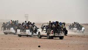 Migrants leave Agadez in central Niger on pick-up trucks, holding wooden sticks tied to the vehicle to avoid falling off, with up to 29 people loaded onto each vehicle