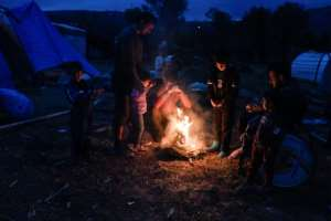 Migrants light a fire in their makeshift camp on Chios island.  By LOUISA GOULIAMAKI (AFP)