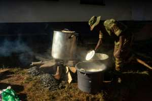 Military help: A soldier prepares breakfast for families sheltered at Ngangu secondary school in Chimanimani. But the most pressing need is for helicopters, to save lives and deliver aid. By ZINYANGE AUNTONY (AFP)