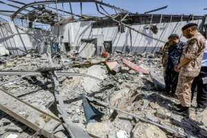 Military officers of the Libyan Government of National Accord (GNA) inspect damage and debris at the migrant detention centre hit overnight by air strikes.  By Mahmud TURKIA (AFP)