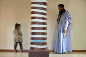 Mohamed El Haiba Ahmed Fal (R), a Moroccan engineer who crossed the wall dividing Morocco and the Polisario-administered side of the Western Sahara poses for a photo with his daughter at his home in the Samara refugee camp in the Western Sahara