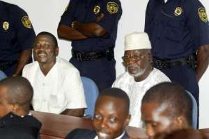 Moinina Fofana, left, dressed in white, pictured on trial in 2004 alongside Sam Hinga Norman. Fofana was to be released on Monday after serving a 15-year term. Norman died in 2007 while awaiting the outcome of his case.  By BEN CURTIS (POOL/AFP)