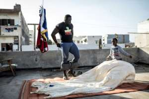 Moussa Diop training on the roof with the help of his nephew.  By JOHN WESSELS (AFP)