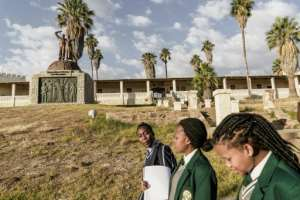 Namibian schoolgirls walk by a memorial in tribute to the victims of the alleged genocide committed by German forces against Herero and Nama people in 1904.  By GIANLUIGI GUERCIA (AFP)