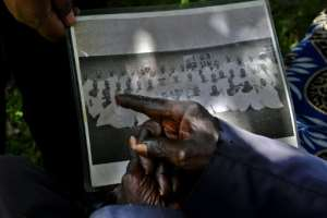 Ngasura, 95, points at a picture of some of the people he was evicted from Kericho with.  By TONY KARUMBA (AFP)