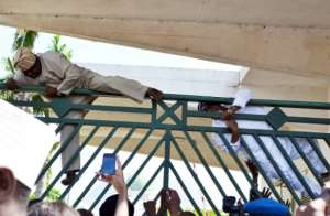 Nigerian MPs climb over the gate of parliament in 2014. Chaotic scenes often abound in the house.  By STR (AFP/File)