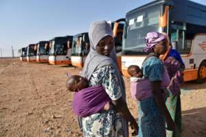 Nigerien migrants wait next to buses in Laghouat in northern Algeria as they are repatriated on June 29, 2018.  By RYAD KRAMDI (AFP)