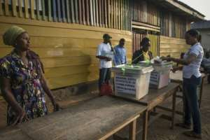 Officials prepare ballots and boxes for the presidential election at a polling station in Kibi, southern Ghana, on December 7, 2016