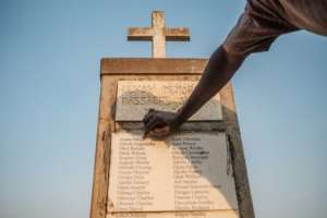 Olanyia Mohammed, 38, escaped a massacre in his village but lost 15 members of his family. He points at his parents names etched on a memorial.  By Sumy Sadurni (AFP)