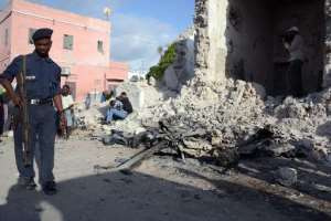A Somali policeman walks past the remains of a car bomb outside Mogadishu's City Palace Hotel on May 31, 2014.  By Mohamed Abdiwahab (AFP)