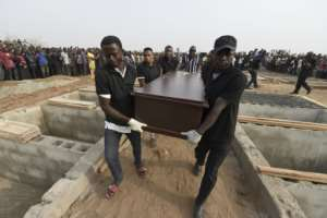 Pall bearers carry coffins during a funeral service last month for people killed during clashes between cattle herders and farmers in Nigeria's Benue state.  By PIUS UTOMI EKPEI (AFP)