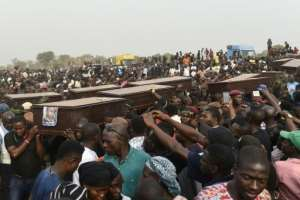 Pall bearers carry coffins during a mass funeral for the scores of people killed during clashes between cattle herders and farmers