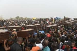 Pall bearers carry coffins during the funeral service for people killed during clashes between cattle herders and farmers.  By PIUS UTOMI EKPEI (AFP/File)
