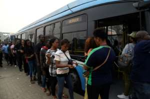 Passengers queue to board a bus provided by the government to offset the impact of the okada and keke ban. Passengers say fares have increased.  By PIUS UTOMI EKPEI (AFP)