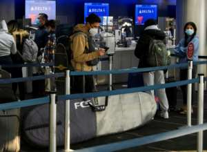 Passengers wait in line to check-in for Delta Air Lines flights at Los Angeles International Airport ahead of the Thanksgiving holiday in Los Angeles, California, on November 25, 2020.  By Patrick T. Fallon (AFP/File)