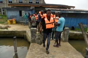 Passengers wearing life jackets prepare to board a speed boat at Bayeku jetty in Lagos. Officials say an awareness campaign on safety is under way.