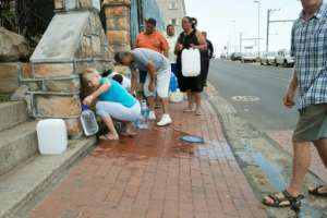 People collect drinking water from pipes fed by an underground spring.  By RODGER BOSCH (AFP/File)