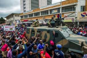 People cheer a Zimbabwe Defense Force military vehicle during a demonstration demanding the resignation of Robert Mugabe