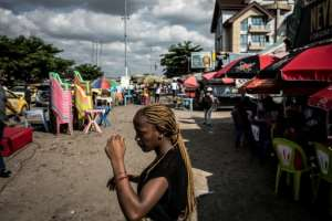 People go about their business in the popular district of Bandal -- but admit the results delay leads them to fear something is badly amiss.  By John WESSELS (AFP)